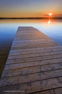 Stretching out like an oasis in the middle of Manitoba, Lake Audy in Riding Mountain National Park is a popular destination for both visitors and residents of Canada. In this picture of a wooden wharf leading off towards the sunset, the lake has been turn