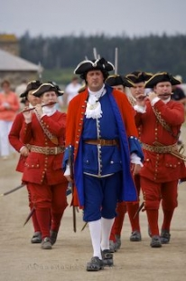 Military people dressed in bright red uniforms except for the head officer, in a march before the cannon gun firing at the Fortress of Louisbourg in Cape Breton, Nova Scotia.