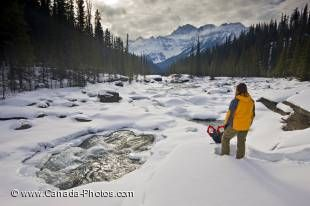 A beautiful scene on the banks of the snowcovered Mistaya River during winter in Banff National Park, Alberta, Canada. Mounta Sarbach towers above the forest in the background while a tourist takes in the scenery.