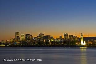 A beautiful dusk picture of the Old Port district in the City of Montreal where the clock tower is lit up as is the horizon behind this city which sits on the shores of the mighty St Lawrence River in Quebec, Canada.