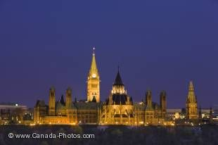 A symbol of Canadian politics, the historic buildings of Parliament Hill in the vibrant city of Ottawa stand out at dusk on the high up on the shores of the Ottawa River in the Province of Ontario, Canada.