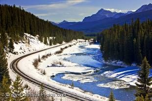 Railway tracks cutting through the canadian Rocky Mountains on a sunny winter day in Banff National Park, Alberta.