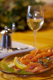 A platter of salmon slices adorns the table at the Rifflin'Hitch Lodge in Southern Labrador, Canada accompanied with a glass of white wine.