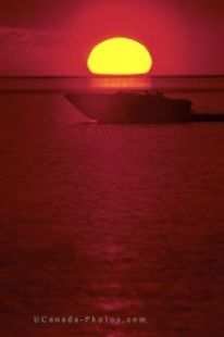 The large yellow glow of the sun sits across the horizon as a boat cruises the waters of Parry Sound, Ontario in the red lighting at sunset.
