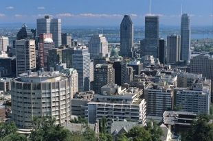 Tall skyscrapers make up the city skyline of Montreal, Quebec in Canada with the St. Lawrence River adorning the backdrop.