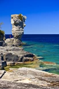 Photo of scenic shoreline and sea Stack along the shore of Flowerpot Island in the Fathom Five National Marine Park, Lake Huron, Ontario, Canada. Model Released.