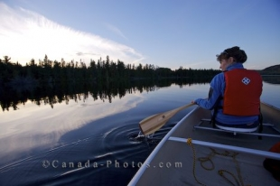 A woman canoeing on Whitefish Lake in Algonquin Provincial Park in Ontario, Canada as the sunset light begins to fade.