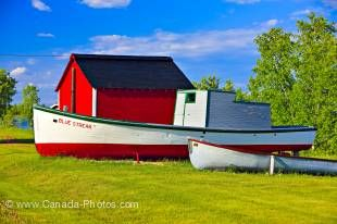 Photo of old wooden fishing boats and red shed in Hecla Village on the shores of Lake Winnipeg, Hecla Island, Manitoba, Canada.